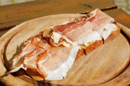 Bread with bacon on a wooden plate