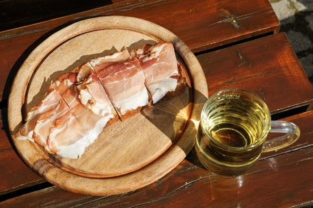 Bread with bacon on a wooden plate and a glass of apple juice Stock Photo