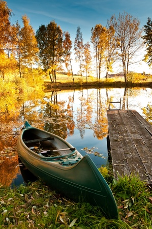 A boat at the shore of a lake. It is autumn. The trees have red and yellow leaves
