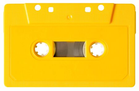 A yellow music cassette. No etiquette is on the cassette, therefore is to writing on