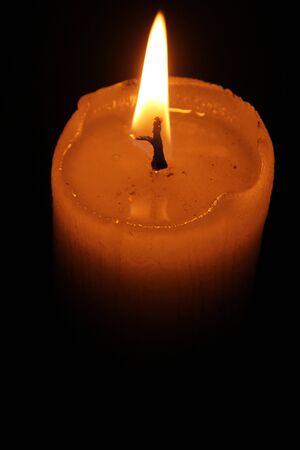 dimly: Dimly lit plain white candle with flame burning Stock Photo