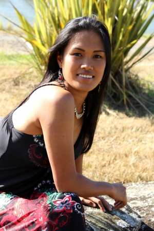 Beautiful Filipina modelling outdoors in red and black dress photo