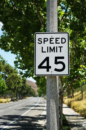45 miles per hour speed limit sign on road side. 스톡 콘텐츠