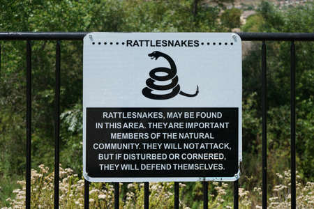 Rattlesnakes warning sign posted inside a park