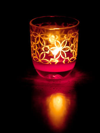 A single lit votive candle in the dark
