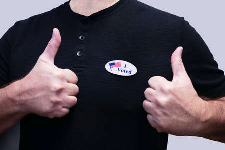 Closeup torso of man in black shirt wearing I Voted sticker giving thumbs after voting. Archivio Fotografico