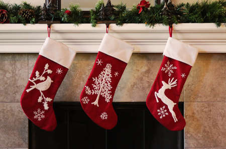 Three red christmas stockings on fireplace mantle Banco de Imagens