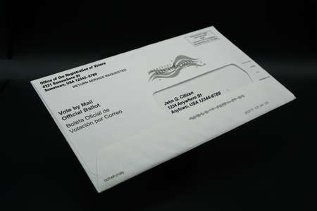 A Vote by Mail Ballot Envelope Isolated on Black