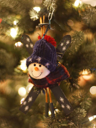 Snowman skier Christmas ornament on tree with focus on snowman's face