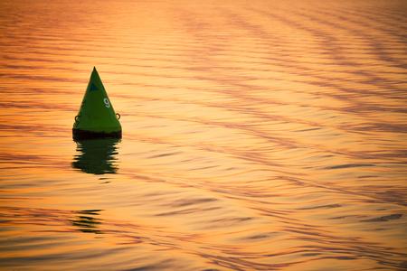 orange water: Small green buoy on waterway into orange water vertical