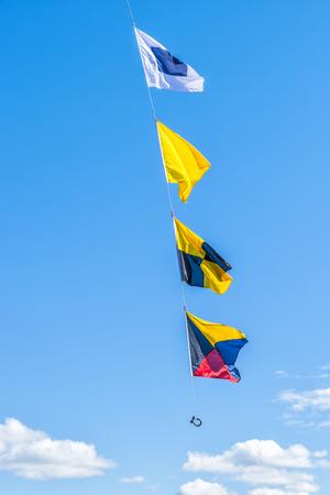 Nautical flags against blue sky.