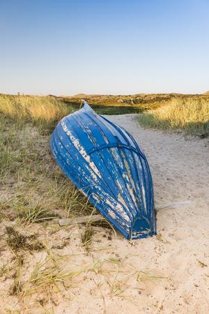 cabeza abajo: Viejo barco de pesca en posición invertida sobre una duna. Foto de archivo