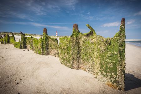 sheet pile: Damaged Larssen sheet pile wall on beach.Lighthouse on background. Sylt. Germany