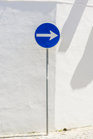 side order: Road-sign on the white wall background.
