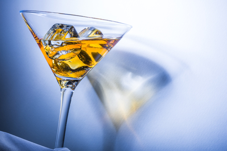 Orange liqueur into a martini glass. Multicolored reflections on the background. Stock Photo