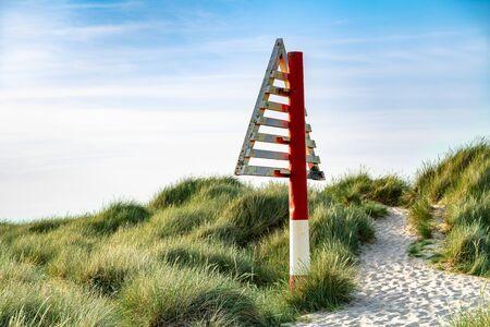 Triangular navigation sign red white on dune