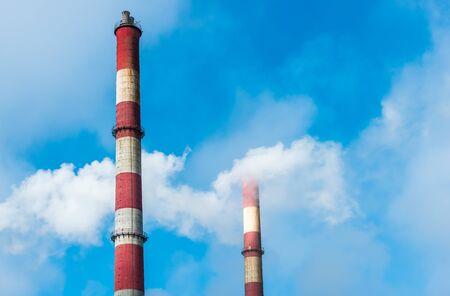 Smoky factory chimney on a background of blue sky.