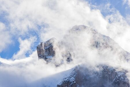 Dolomite Mountains covered with clouds in winter, view for the Brunecker Turm. Standard-Bild