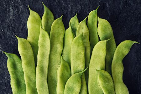 Green flat beans in pods lie on a stone slab. Top view.