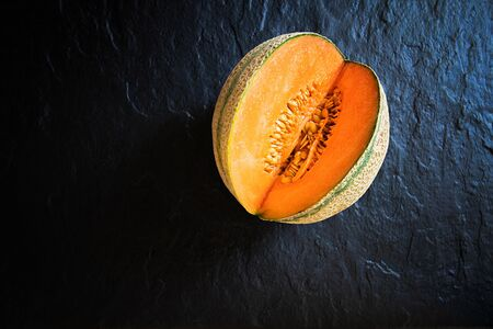 Small, cut melon lying on a stone slab. View from above.