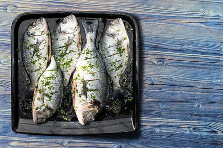 Five fresh fish prepared for baking lying on the baking plate. View from above. Standard-Bild