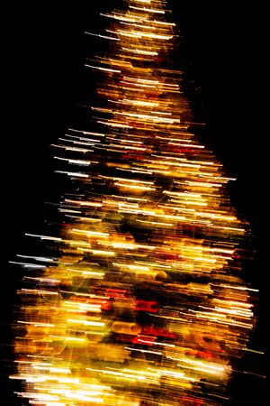 Christmas tree with decorations on a black background. Photo blurred. Standard-Bild