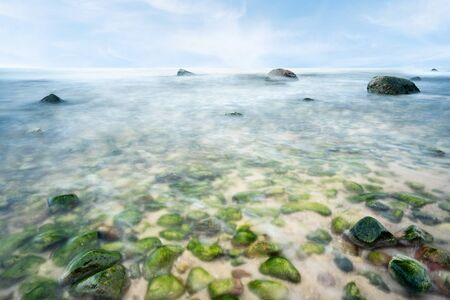 A view of the rocky beach in Miedzyzdroje. Baltic sea. Stones into the water. Blurry effect with long exposure.