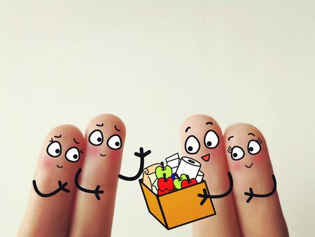 Four fingers are decorated as four person. Two of them is sending a food parcel to two friends. They are kind. 写真素材
