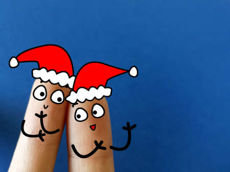 Two fingers are decorated as two person. They are celebrating christmas. Zdjęcie Seryjne
