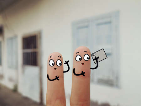 Two fingers are decorated as two person. They are at the back yard.They are taking video happily. Stock Photo