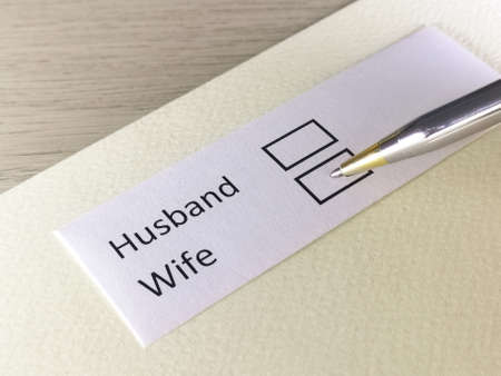 One person is answering question on a piece of paper. The person is thinking to choose husband or wife.