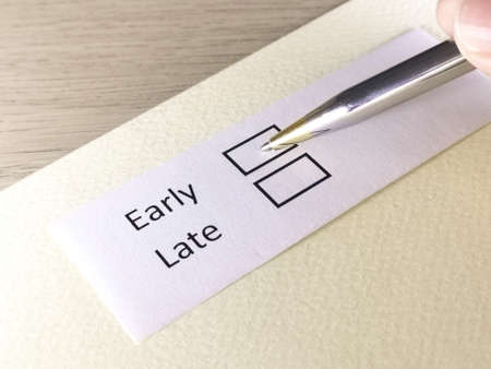 One person is answering question on a piece of paper. The person is thinking to be early or late.