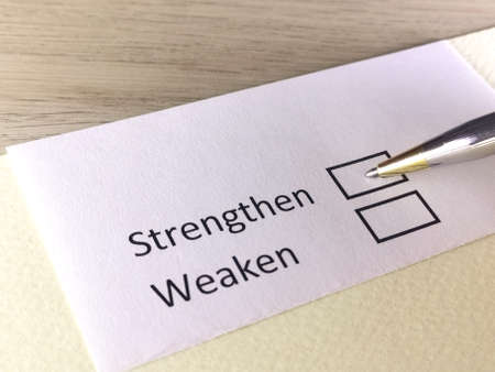 One person is answering question on a piece of paper. The person is thinking to strengthen or to weaken.