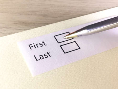 One person is answering question on a piece of paper. The person is thinking to be the first or the last.