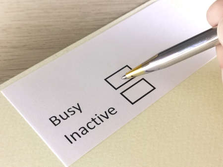 One person is answering question on a piece of paper. The person is thinking to be busy or inactive.
