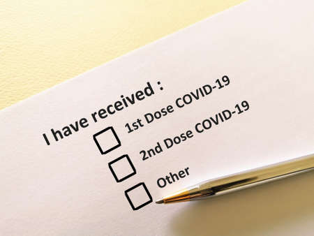 One person is answering question about vaccines. The person is filling up COVID-19 record card.