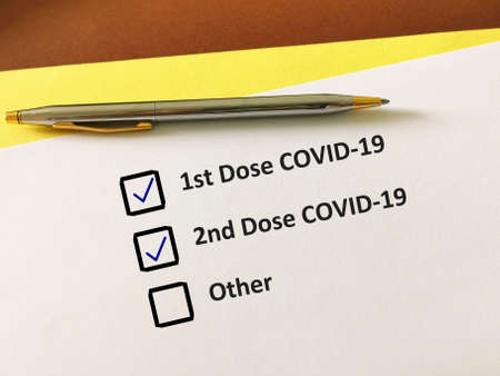 One person is answering question about vaccines. The person is filling up COVID-19 record card. Stock fotó