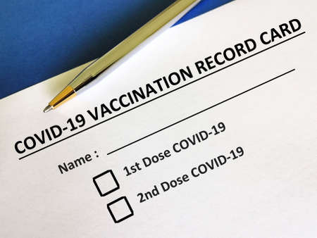 One person is answering question about vaccines. The person is filling up COVID-19 vaccination record card.