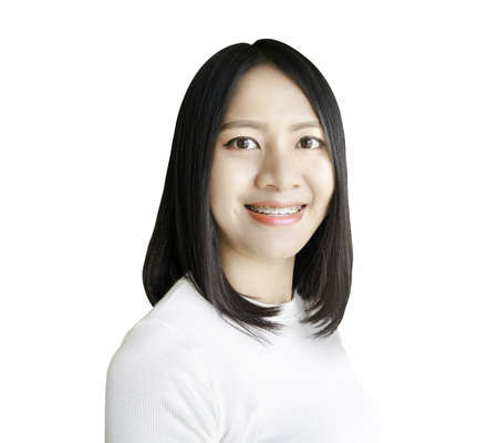 Lovely Asian young woman wearing braces smiling isolated on white background blurred photo.