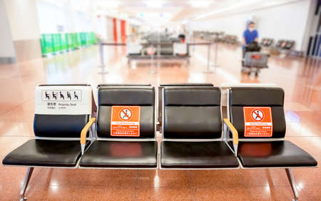 ''Social Distancing Please do not seat here'' Sign on empty black chair in international airport with gap for prevent coronavirus (COVID-19),New normal concept,blurred photo.