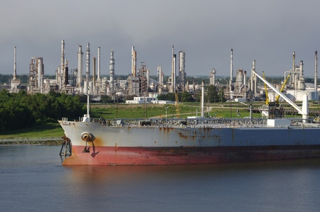 Oil refinery on the mississippi river near the gulf entrance with tanker ship in the foreground Imagens