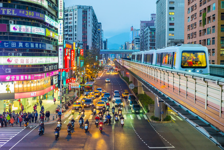 Street view of Taipei with metro train approaching Zhongxiao Fuxing Station. The Taipei MRT is one of the best way to travel around the city.