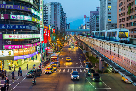best way: Street view of Taipei with metro train approaching Zhongxiao Fuxing Station. The Taipei MRT is one of the best way to travel around the city.