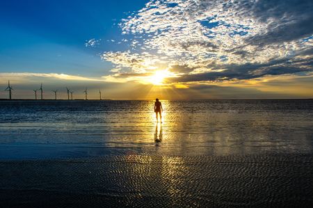 sillouette of a man and Wind turbine array at Gaomei Wetlands Stock Photo