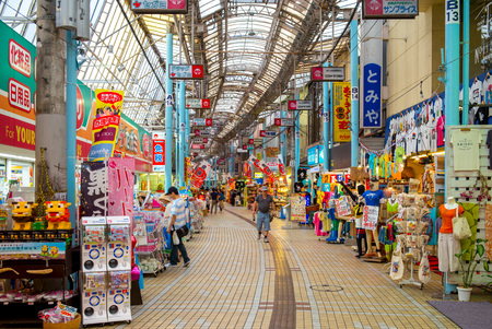 Street view of Heiwa Dori, a covered shopping arcade featuring many shops and vendors that sell local wares Éditoriale