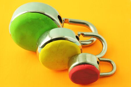 Multiple levels of security depicted with color coded padlocks on a yellow background Stock Photo - 16479001