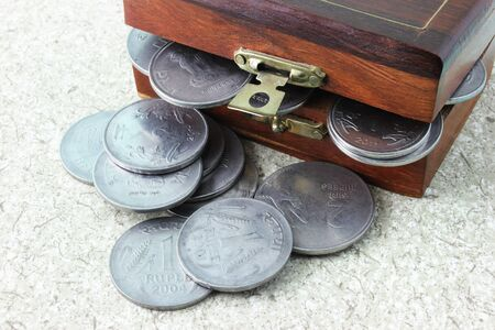 Indian currency coins overflowing from a wooden chest