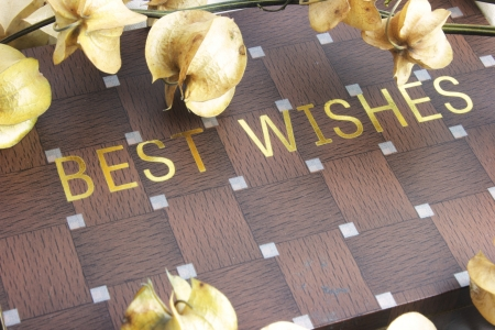 Best wishes inscribed on wooden checkerboard box, placed amidst dried cape gooseberries