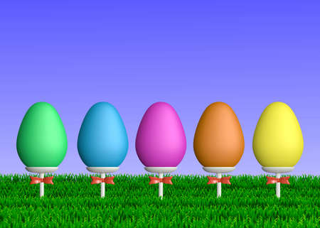 Row of colorful Easter eggs on ceramic sticks with ribbon bows placed in green grass. Stock Photo