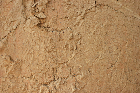 Background texture of mud wall plaster with cracks